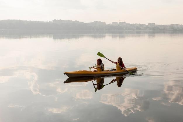 Long shot women rowing in kayak