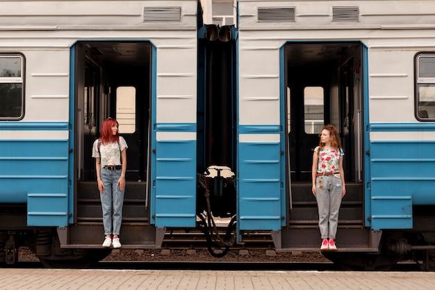 電車の出入り口に立っているロングショットの女性