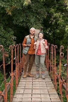 Длинный выстрел молодая пара, идущая по деревянному мосту