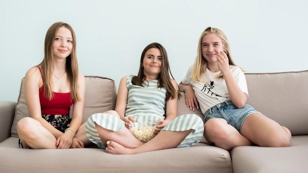 Long shot young girls watching a movie