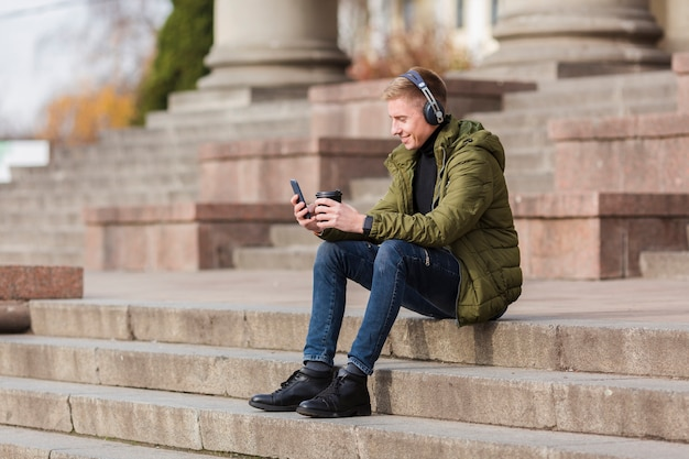 Long shot young man listening to music on headphones outside