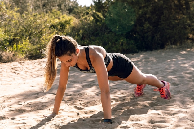Long shot young woman doing push ups on sand