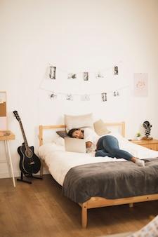 寝室でラップトップを探しているロングショットの若い女性