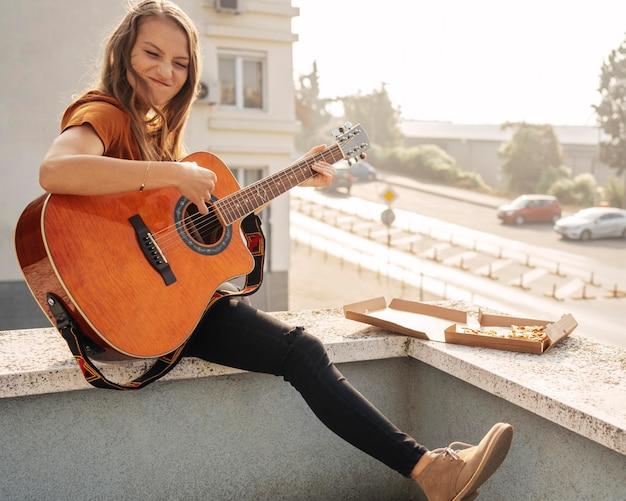 롱 샷된 젊은 여자 기타 연주