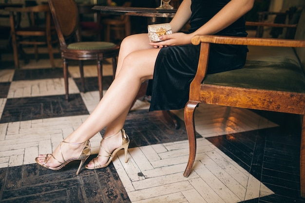 Long skinny legs wearing high heeled sandals shoes, fashion details of elegant beautiful woman sitting in vintage cafe in black velvet dress, rich stylish lady, elegant trend footwear