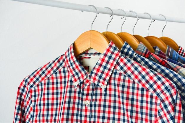 木製のハンガーの長い袖のチェッカーのシャツは、白い背景の上に服のラックにハングアップ