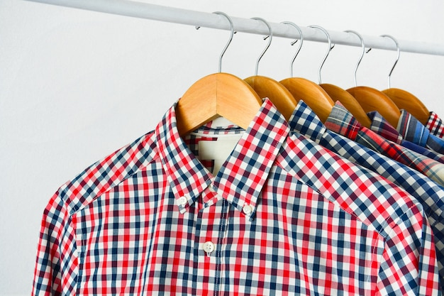 Long sleeve checkered shirt on wooden hanger hang on clothing rack over white background
