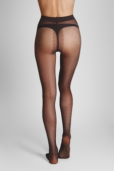 Long slim female legs in transparent tights with a classic polka dot pattern.