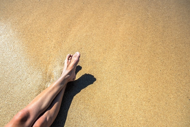 Long slim young woman legs relaxing lying down and sunbathing on sand tropical beach under hot sun in summer