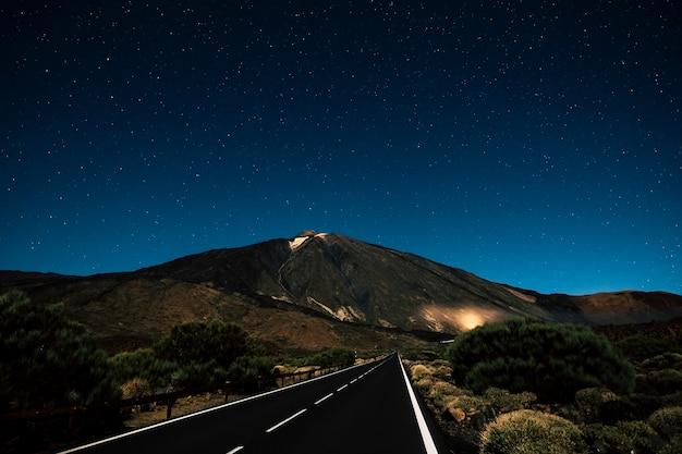 夜は空が星でいっぱいの真っ直ぐなアスファルトの黒い道