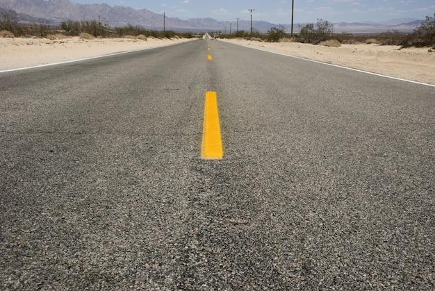 デスバレーの砂漠の風景を通る長くまっすぐなアスファルト道路
