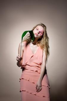 長くスタイリッシュなドレス。緑の葉と顔の近くの花でポーズをとる長いスタイリッシュなドレスを着ている金髪モデル