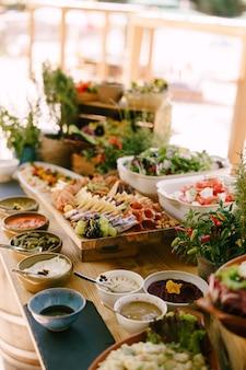 Длинный стол с готовыми банкетными лакомствами и цветочными горшками на размытом фоне