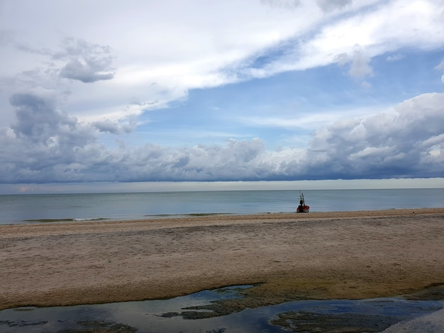 Long tail boat on the beach with sea and nimbus clouds in the sky