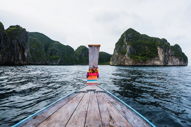 Long-tail boat floating in transparent water of phi-phi island, maya bay, the paradise island in thailandia.