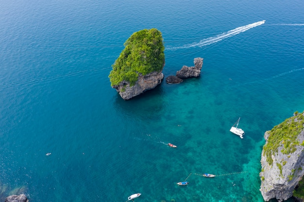 Long tail and speed boat chartered for snorkelling at phi phi island in the tourist high season of phi phi island kra bi province thailand