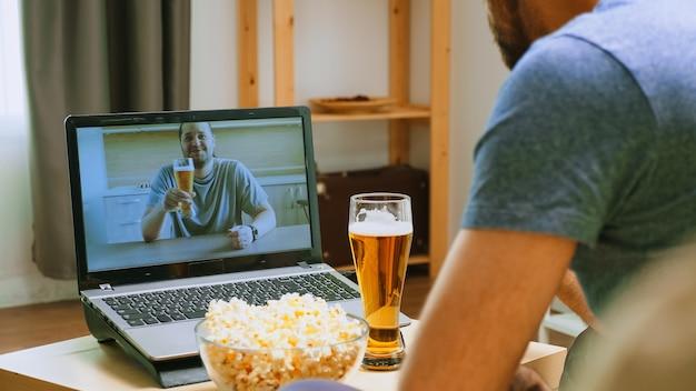 오랜 친구가 화상 통화를 하고 전 세계적으로 전염병이 돌고 있는 시기에 맥주를 마십니다.