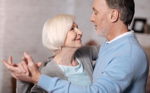 Давно вместе. крупным планом портрет счастливого старшего мужчины и женщины, стоящих и смотрящих друг на друга во время танцев.