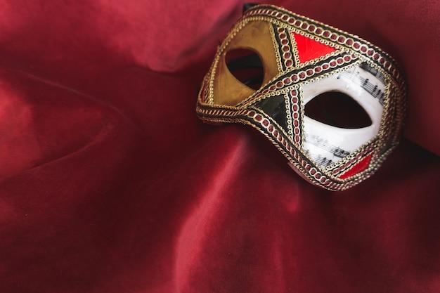 Maschera veneziana lunga su un tessuto rosso