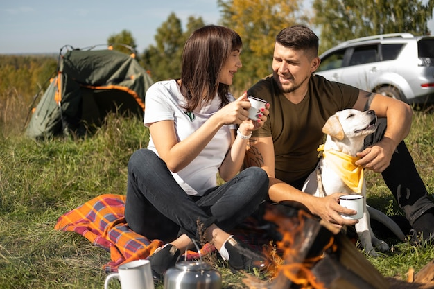 ロングビューかわいいカップルと犬が屋外で時間を過ごす
