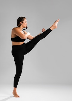 Long view of karate woman giving a kick