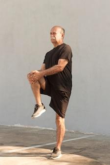 Vista lunga dell'uomo che allunga le gambe