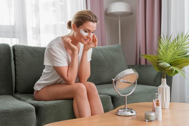Длинный взгляд женщины используя обработку мешков под глазами