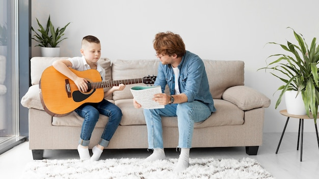 Long view student and teacher playing guitar