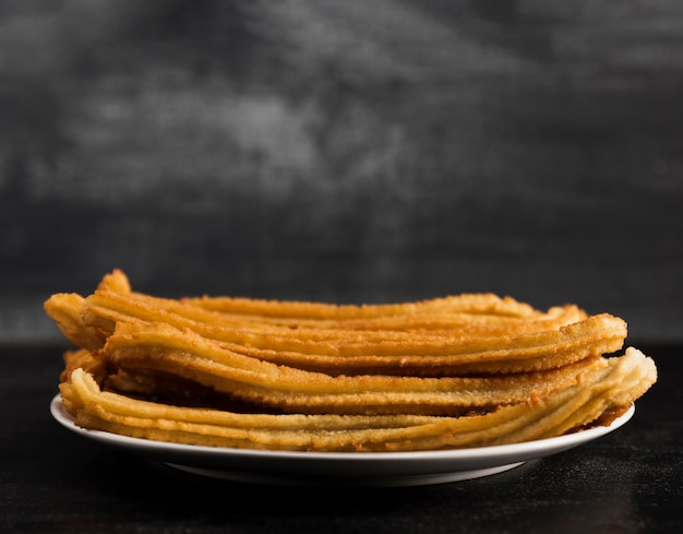 Long view of white plate filled with churros