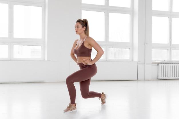 Vista lunga della donna che fa le esercitazioni