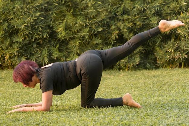 Vista lunga della donna che fa esercizi per le gambe