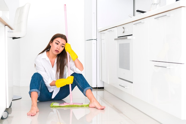 Long view of woman holding a mop and sitting on the floor