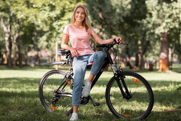 Женщина с длинным видом, отдыхая на велосипеде