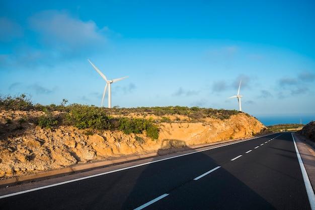 Долгая асфальтовая дорога с ветряными мельницами на заднем плане
