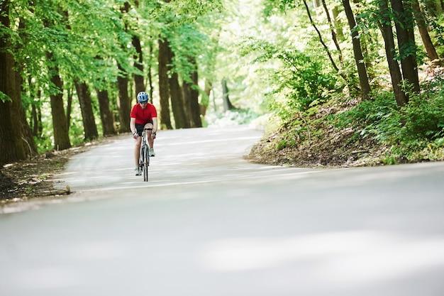 長い道のり。自転車のサイクリストは晴れた日に森のアスファルト道路に
