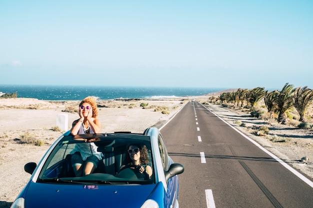 長い道のりと友人は、休暇のために運転している若い女性のカップルと自由と独立の概念で一緒に旅行します