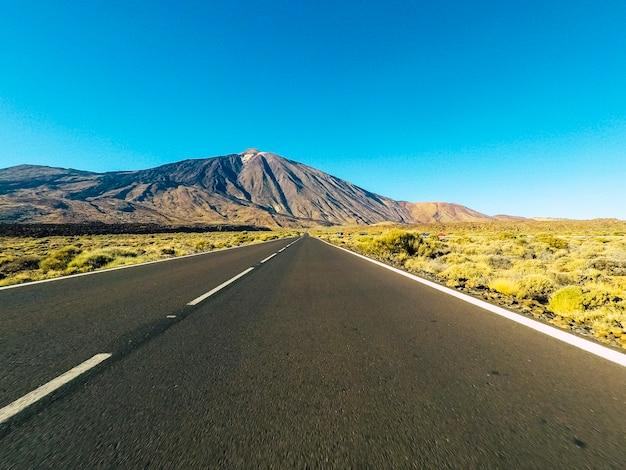 バルカンマウントが正面にあり、青い澄んだ空がある山の長い道のり-黒いアスファルトと白い線のある地上の視点-運転と旅行のコンセプト