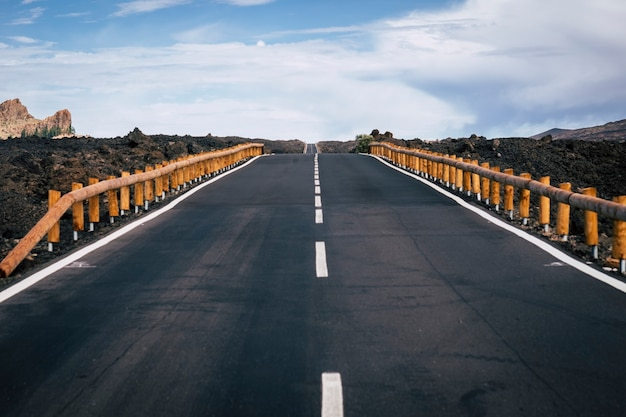중간 및 무한 방향 및 이동 거리 개념에 흰색 직선이있는 아스팔트의 먼 길. 여행자와 모험 개념에 대 한 주위 아스팔트와 산. 차도 사람도 없다