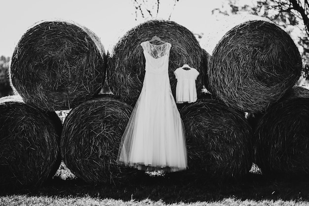 Long wedding dress and little dress for child hang on hay rolls
