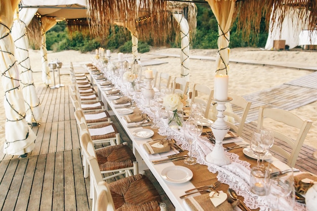 Long white dinner table with sparkling glassware and candleholders stands on the beach