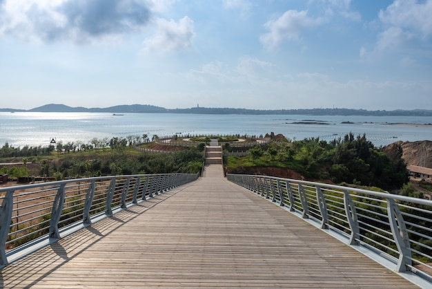 The long and wide wooden passage under the blue sky and white clouds leads to the distance Premium Photo