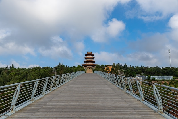 The long and wide wooden passage under the blue sky and white clouds leads to the distance