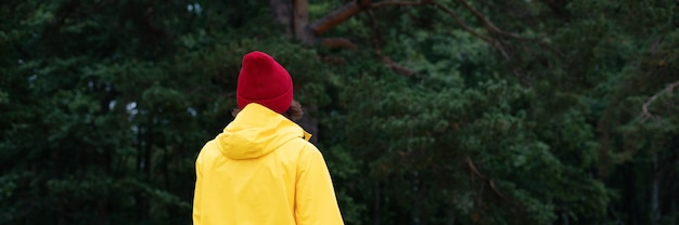 Знамя длинной ширины с видом сзади женщины в сосновом лесу в осенний день. местные путешествия и приключения