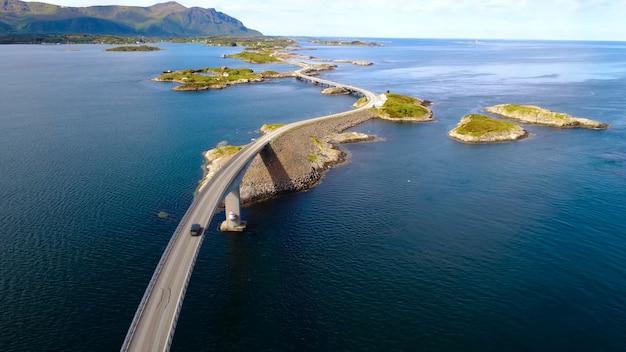 Длинный извилистый мост, идущий над островами, горы, хорошая погода.