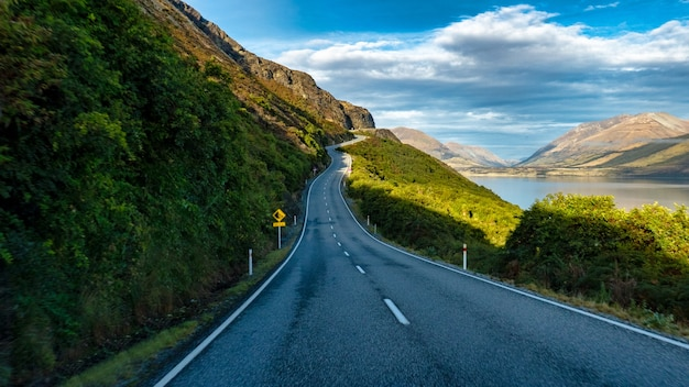 Long and winding highway on the edge of the stunning lake wakatipu near queenstown bordered by the southern alps