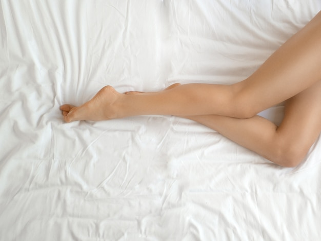 Long woman legs with smooth soft skin. close up of female with perfect healthy silky legs skin after hair removal on white bed in light interior. beauty, skin care concept