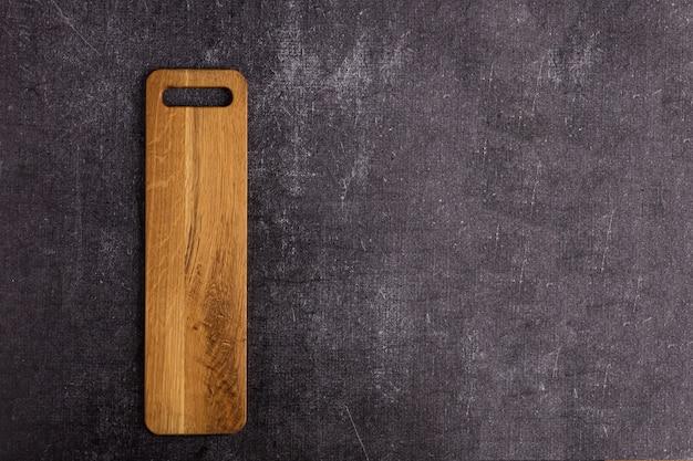 Long wooden cutting board on dark background