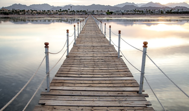 Long wooden pier among the sea with mountains on the horizon at sunset.