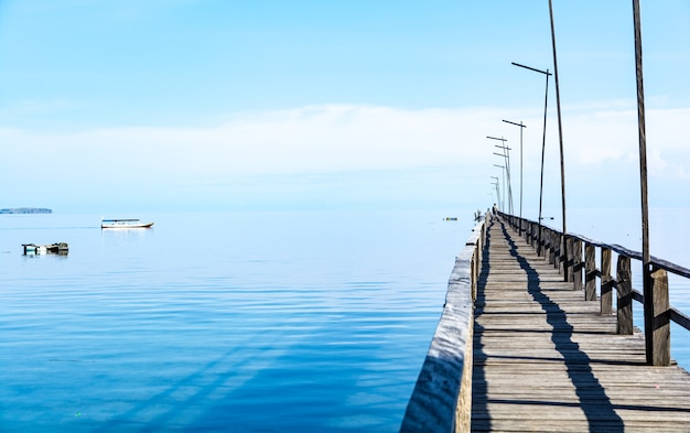 A long wooden pier on clear turquoise water