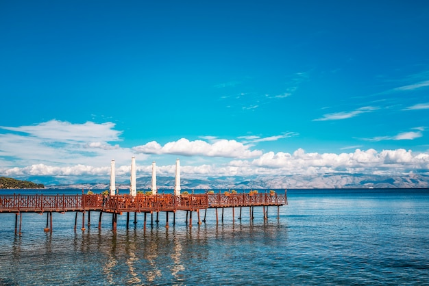Long wooden pier with romantic cafe in end in ionian sea. greece. beautiful lanscape, mountains on sealine. sunny day with clouds on corfu island.